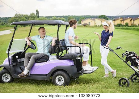 Family day on the green. Smiling golfing companions on green with their golf cart, discussing game