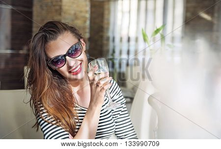 Closeup portrait of young female customer drinking white wine