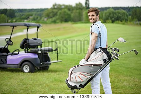 Enjoying fine day on green. Smiling young guy walking away along green golf course, holding golf back and looking over his shoulder with golf cart on background