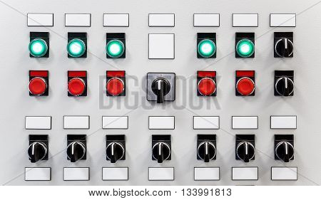 Control panel of industrial equipment with name plates switches red buttons and glowing green buttons