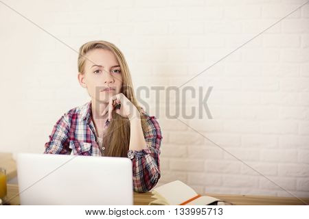 Attractive caucasian girl sitting at office desk with laptop orange juice and laptop on white brick wall background