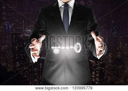 Man holding levitating key on abstract dark city background with business charts