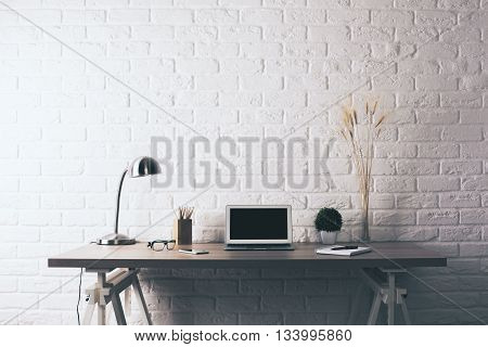 Front view of creative wooden designer desktop with blank laptop decorative plants table lamp glasses and stationery items on white brick wall background. Mock up poster