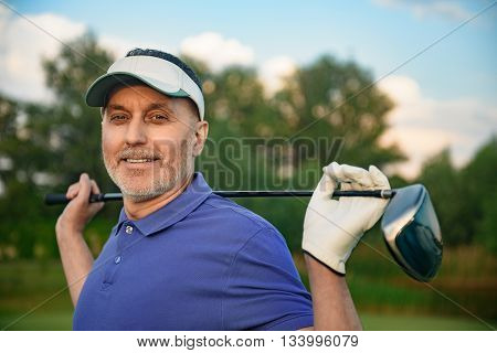 It is great day for golf. Mature man holding his golf club over his shoulders