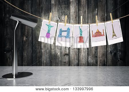 Travel concept with table lamp next to pictures of sights hanging on a rope with pegs on wooden plank background