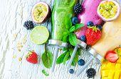 Berry and fruit smoothie in bottles healthy summer detox yogurt drink diet or vegan food concept fresh vitamins mango lime poster