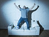 young man fanatic and crazy football fan watching television soccer match with ball jumping on sofa couch screaming happy celebrating goal in ecstasy poster