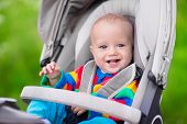 Baby boy in warm colorful knitted jacket sitting in modern stroller on a walk in a park. Child in buggy. Little kid in a pushchair. Traveling with young kids. Transportation for family with infant. poster