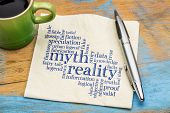 myth versus reality word cloud - handwriting on a napkin with cup of coffee poster