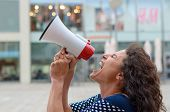 Young woman protester standing in an urban street shouting into a megaphone airing her grievances close up profile head shot poster