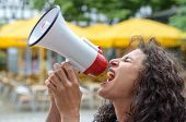 Angry young woman using a loud hailer or megaphone outdoors in an urban square during a protest or demonstration poster