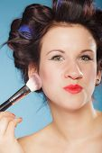 Cosmetic beauty procedures and makeover concept. Woman in hair curlers applying makeup blusher with brush. Girl gets blush on cheekbones on blue poster