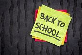 back to school reminder note - handwriting on a sticky note against black Nepalese lokta paper poster