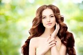 Model with long wavy hair. Waves Curls Hairstyle. Hair Salon. Updo. Fashion model with shiny hair. Woman with healthy hair girl with luxurious haircut. Hair loss Girl with hair volume. Brunette poster