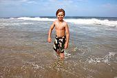 cute boy has fun in the stormy beach poster