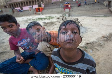 VARANASI, INDIA - MAR 16, 2018: Unidentified indian street children on the banks of Ganga river. According to legends, the city was founded by God Shiva about 5000 years ago.