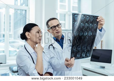 Knowledgeable Look. Professional Doctors With Brain Tumors While Looking At Mri Scan