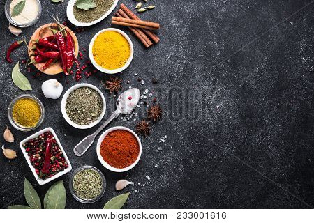 Set Of Various Spices And Herbs On Black Stone Table. Top View With Copy Space. Food Background.