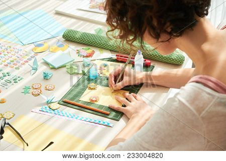 Young Curly Woman Making Colorful Greeting Card For Her Mother While Sitting At Wooden Table, Decora