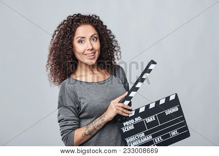 Excited Curly Female Holding Movie Clapper Board, Slate Film.