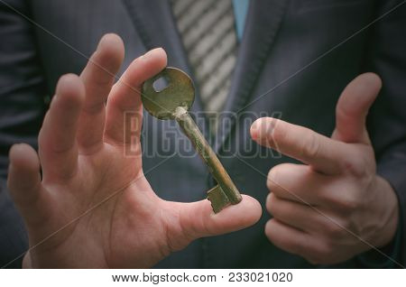 Key To Success Concept. Businessman Holding In Hands An Old Rusty Key. Explanation Of Information De