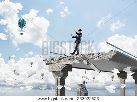 Businessman Walking Blindfolded Among Flying Paper Planes On Concrete Bridge With Huge Gap As Symbol