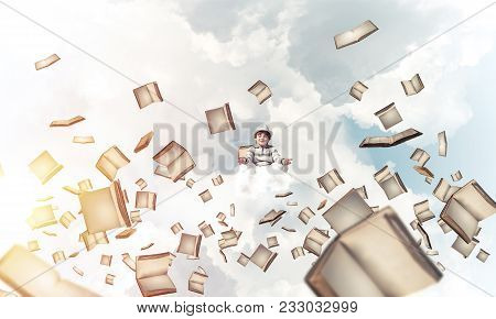 Young Little Boy Keeping Eyes Closed And Looking Concentrated While Meditating Among Flying Books In