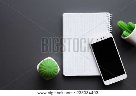 Blank Opened White Notebook, Black Screen Smartphone And Cacti Potted On Grey Office Desk Background