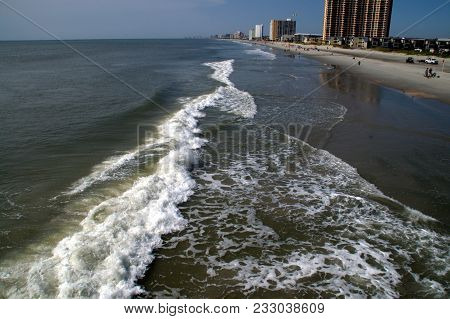 Waves Rolling In Along The Atlantic Coast Shoreline With Hotels In The Background