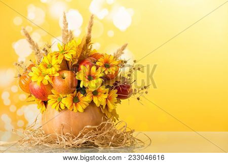 Original Composition Of Fruit, Flowers And Thorns In Pumpkin On Mat Made Of Sisal On Yellow Backgrou