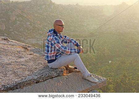A Handsome Bald Man In Glasses Sits On A Sunset Or Dawn Background In Hampi, On The Top Of The Mount