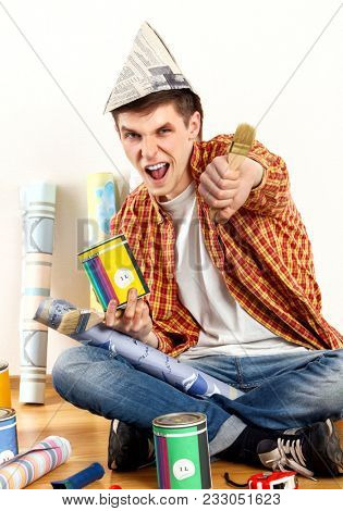 Repair home man holding paint roller for wallpaper. Tired and frustrated mad male in newspaper cap renovation apartment. Paint bank and paint brush in hand. Loan for housing for students.