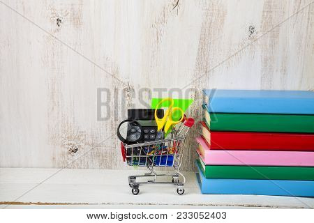 Items For School In A Shopping Trolley And Books On A Wooden Background. Concept Of Buying Items For