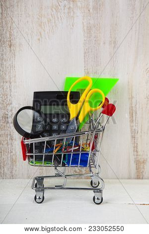 Items For School In A Shopping Trolley On A Wooden Background. Concept Of Buying Items For School.