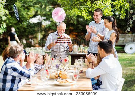 Family Celebration Outside In The Backyard. Big Garden Party. Birthday Party. A Senior Man Holding A
