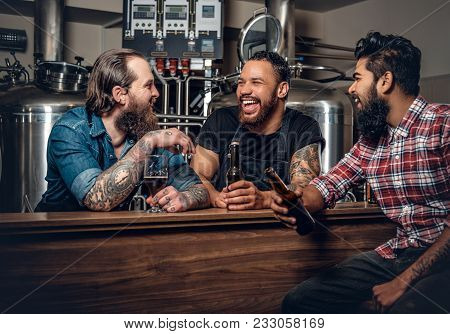 Stylish Bearded Tattooed Caucasian, Black And Indian Men Drinking Craft Beer In The Microbrewery.