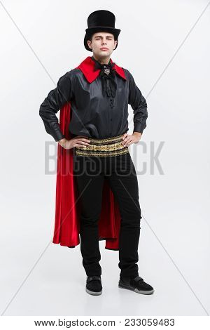 Vampire Halloween Concept - Full Length Portrait Of Handsome Caucasian Vampire In Black And Red Hall