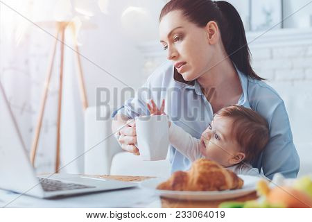 Very Busy. Serious Attractive Good Looking Woman Holding A Cup Of Tea And Talking On The Phone While