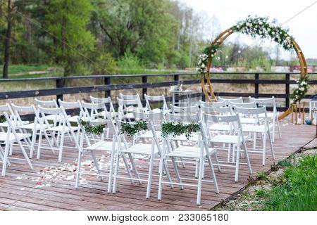 Area Of The Wedding Ceremony In Forest, Near River On The Pier. Wooden Round Arch, White Chairs Deco