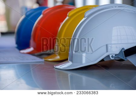 Blueprint And White, Blue, Red And Yellow Hard Safety Helmet Hat On The Table For Safety Project Of