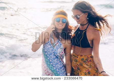 Two boho friends (girls) wearing floral maxi dress and skirt walking on the sea shore. Bohemian clothing style.