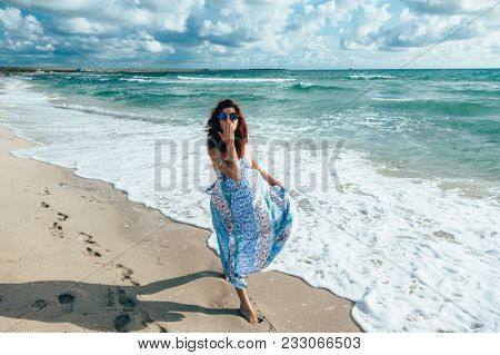 Woman wearing ethnic flying dress walking barefoot at the beach