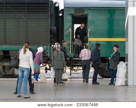 Chisinau, Moldova - 11 May, 2016: A Conductor Of A Train Is Helping A Lady With Her Luggage In The T