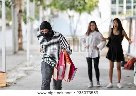 Thief Run Away After Stealing Shopping Bag From Women On Street.with Blurry Victim Woman Upset Backg