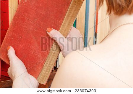 Woman Is Taking An Old Book From A Bookshelf. Many Hardback Books On Wooden Shelf. Library Concept