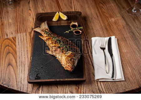 Main Dish In The Restaurant. Grilled Grilled Trout With Lemon And Lettuce Leaves