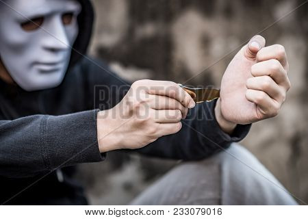 Mystery man in white mask wearing hoody jacket try to cut his wrist with the debris of broken bottle. depression self destruction suicidal addiction. major depressive disorder concept poster