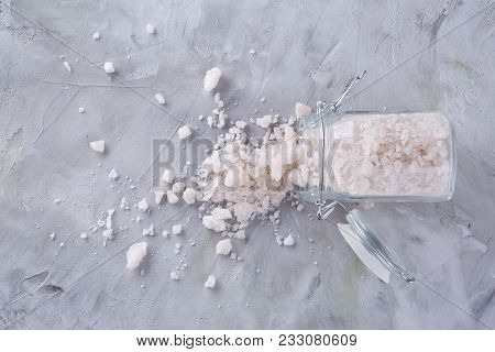 Spa Concept. Bath Salt Pouring Out Of Glass Jar On White Textured Background, Close-up, Selective Fo