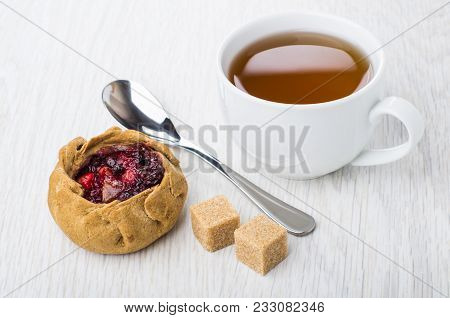 Pie With Cowberries, Brown Sugar, Tea In Cup And Spoon On Wooden Table