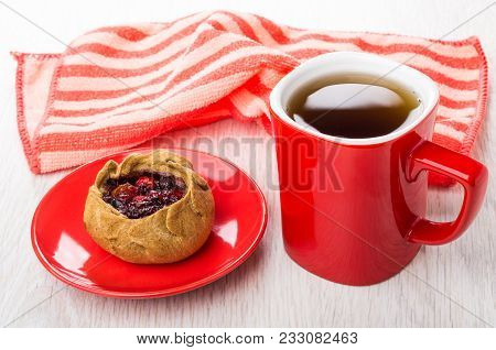 Pie With Cowberries In Red Saucer, Striped Napkin, Cup Of Tea On Wooden Table